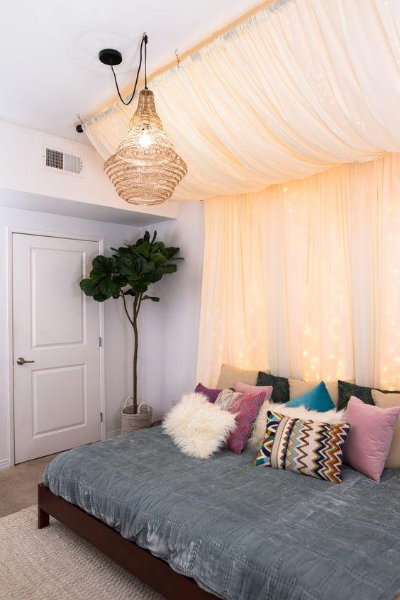 un baldacchino pastello con luci sopra il letto e un paralume in vimini per un look boho