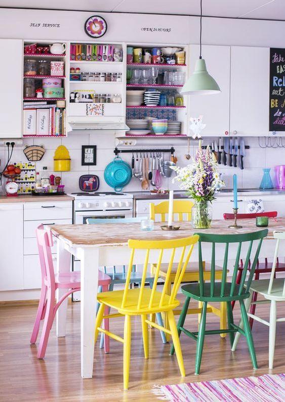 sedie colorate non corrispondenti e stoviglie e scaffali colorati rendono lo spazio audace e allegro