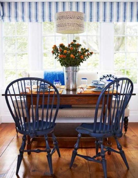 uno spazio da pranzo ispirato alla spiaggia con sedie blu scuro e tocchi di blu audace più un paralume stampato