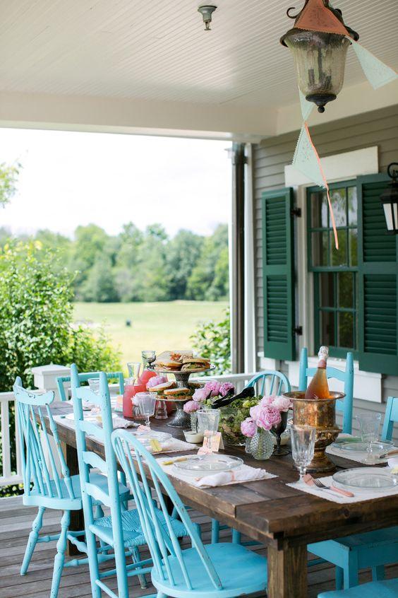 sedie blu non corrispondenti rendono lo spazio da pranzo all'aperto audace e infuso di colore, rinfrescano questa zona