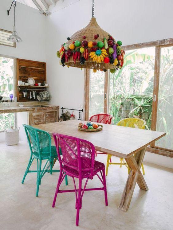 sedie in vimini dipinte e un paralume in vimini decorato con frutta finta per uno spazio da pranzo tropicale