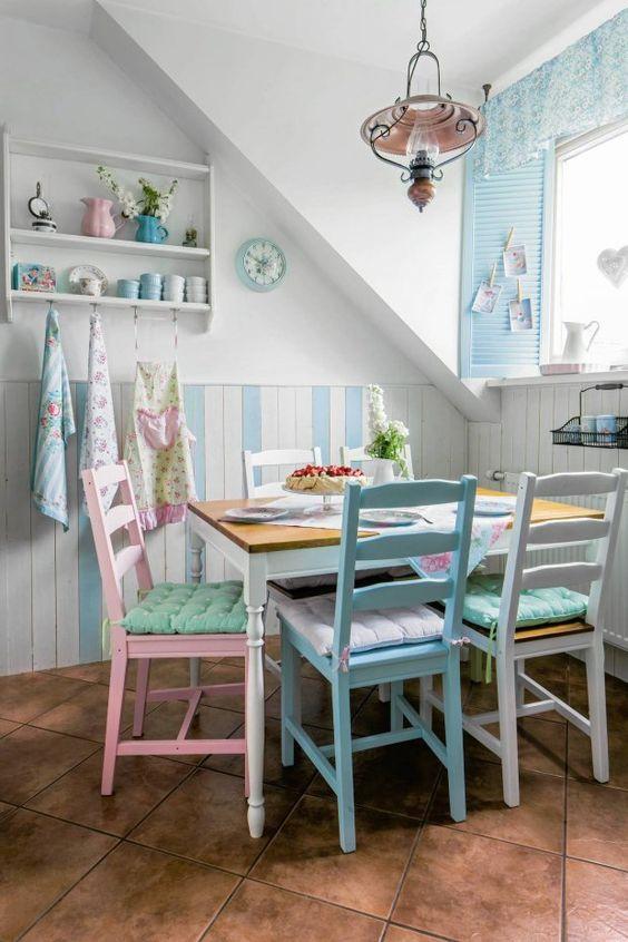 un angolo pranzo di ispirazione vintage con sedie pastello dello stesso design e tocchi di azzurro polvere