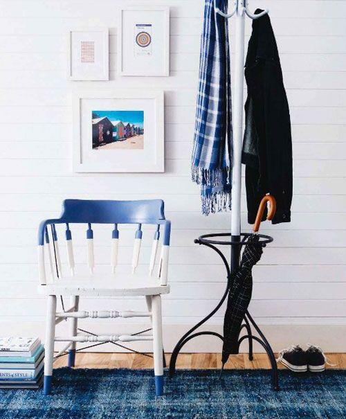 una sedia blu navy e bianca a blocchi di colore e gambe tuffate è l'ideale per un ingresso ispirato alla spiaggia