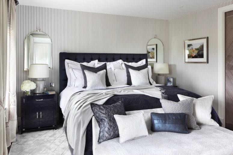 una lussuosa camera da letto d'ispirazione vintage con pareti gessate e uno splendido letto imperatore imbottito blu navy, tessuti e accessori grigi e blu scuro