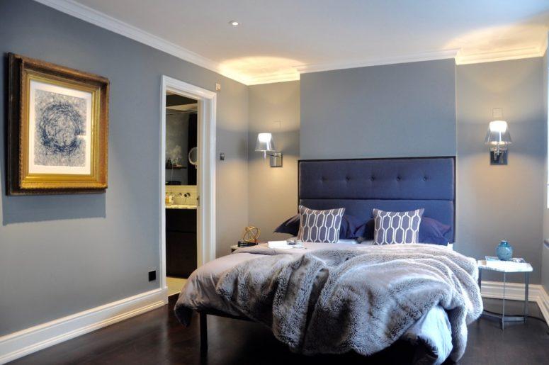 una camera da letto contemporanea con pareti e mobili grigi e uno splendido letto blu scuro imbottito più cuscini grigi e una coperta