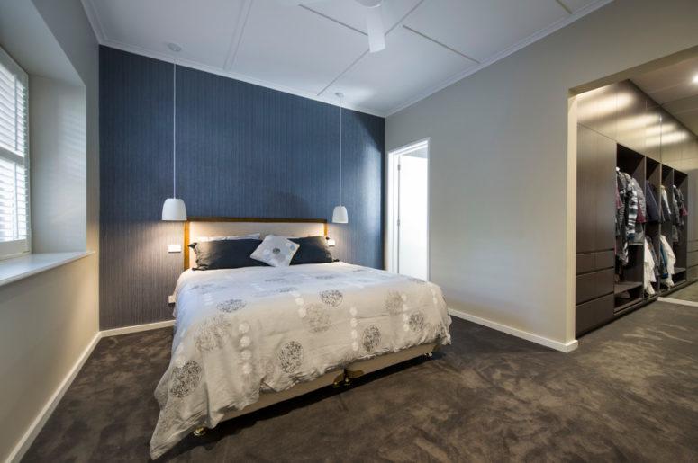 una camera da letto contemporanea con pareti grigio tortora e un pavimento in moquette grigio grafite, con una parete blu navy e un letto grigio