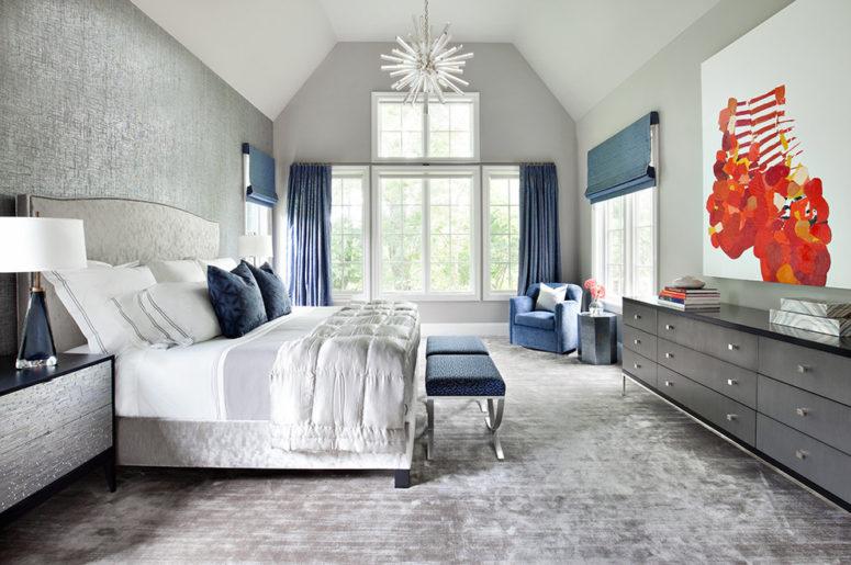 una lussuosa camera da letto grigia punteggiata di accenti blu navy: sgabelli, tende, sfumature romane e cuscini
