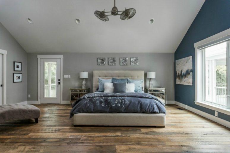 una camera da letto mansardata in grigio tortora con una parete blu e biancheria da letto blu