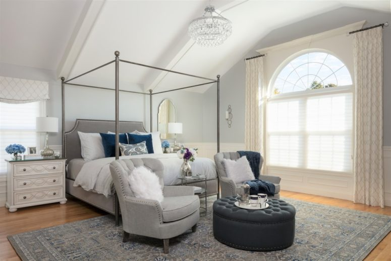 un'accogliente camera da letto con mobili grigio tortora e un tappeto grigio più alcuni accenti blu scuro come cuscini