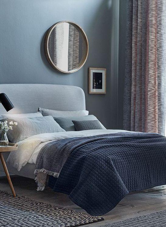 una camera da letto blu con pavimenti grigio chiaro e un letto imbottito grigio chiaro più biancheria da letto grigia