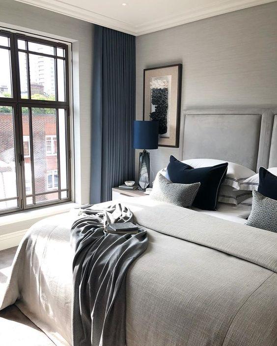 una camera da letto color tortora con tocchi blu audaci mostra lusso e bellezza