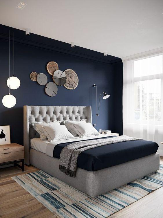 una camera da letto chic con un muro blu navy, un letto imbottito grigio, alcune luci e lampade accattivanti