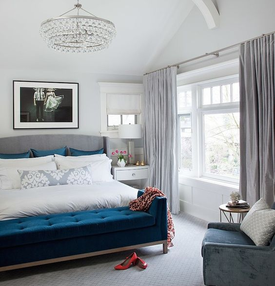 una camera da letto color tortora e crema con una panca blu scuro, cuscini e una sedia blu