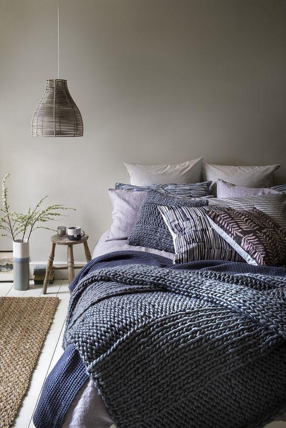 una camera da letto grigio tortora con lenzuola a strati blu navy e blu e un paralume in vimini