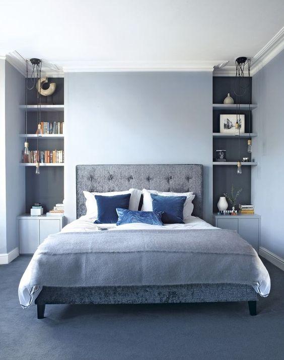 una camera da letto azzurra con nicchie grigie, un letto e un pavimento imbottiti grigi e accenti blu audaci