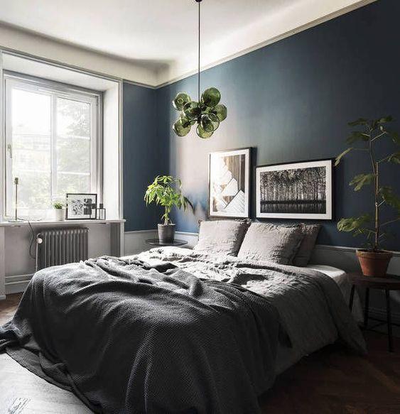 una camera da letto elegante e rilassante in grigio e con un muro blu navy, con vegetazione e accenti verdi