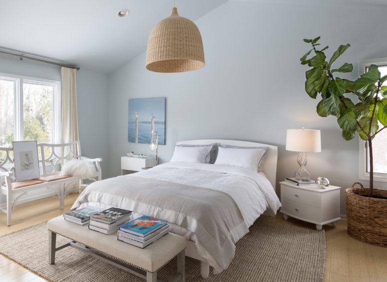 una camera da letto color crema, tortora e celeste con paralume in vimini, alcuni tessuti grigi e mobili color crema