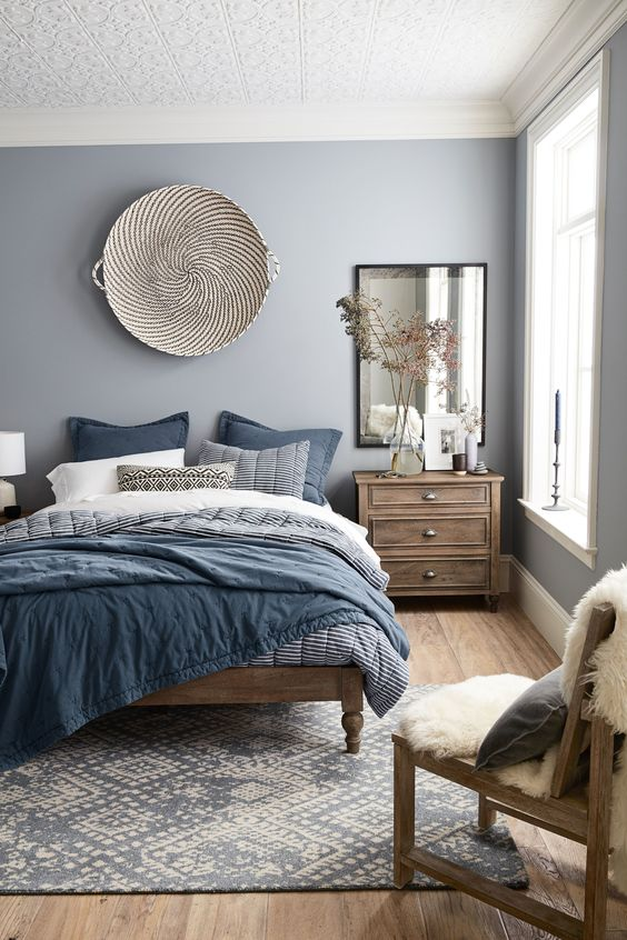 un'accogliente camera da letto grigio chiaro con mobili in legno e biancheria da letto blu