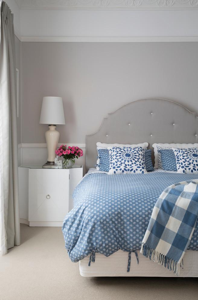 classici moderni ed eleganti: pareti, tende, pavimento e mobili grigio tortora e biancheria da letto blu sul letto