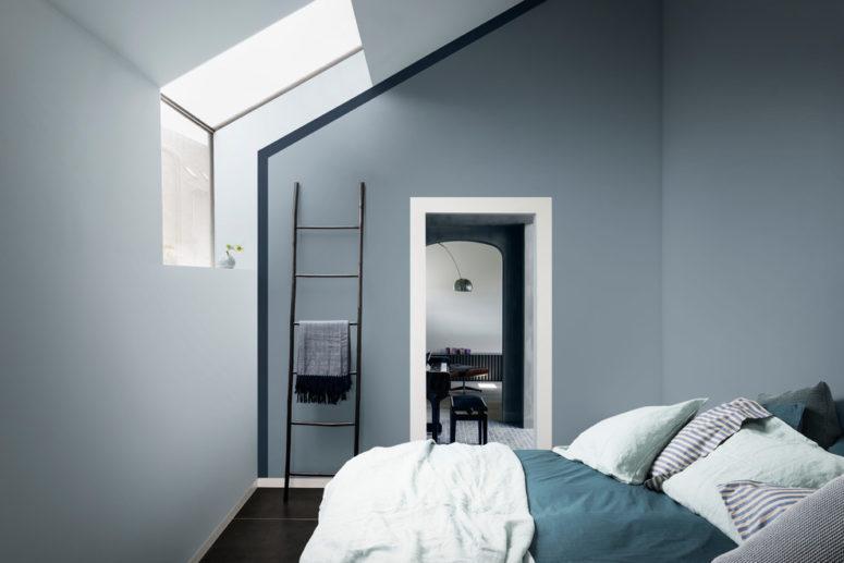 una camera da letto mansardata piccola e minimalista realizzata in blu lunatico e con lenzuola verde acqua e turchese