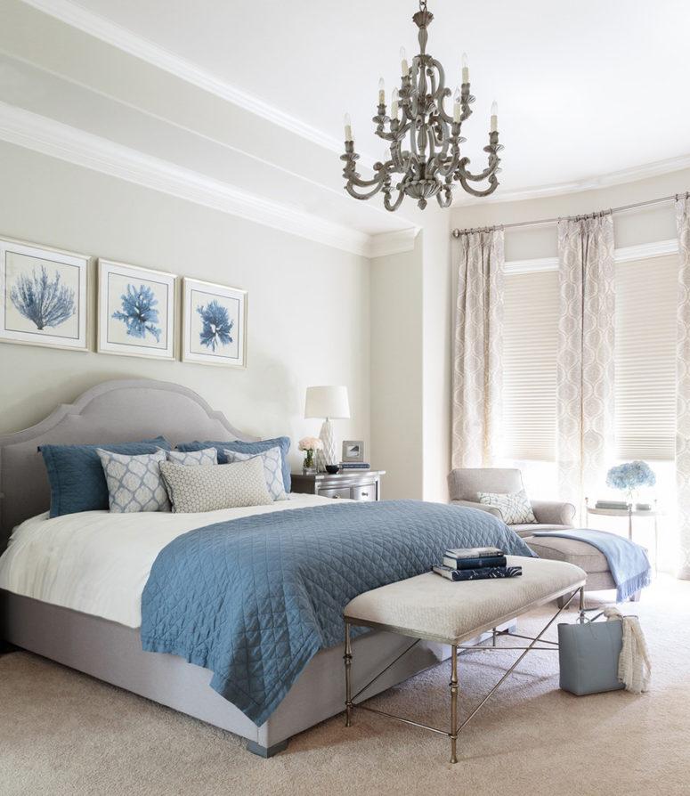 una camera da letto ispirata al mare con pavimento grigio, pareti, tende e un letto imbottito, oltre a tessuti e opere d'arte blu