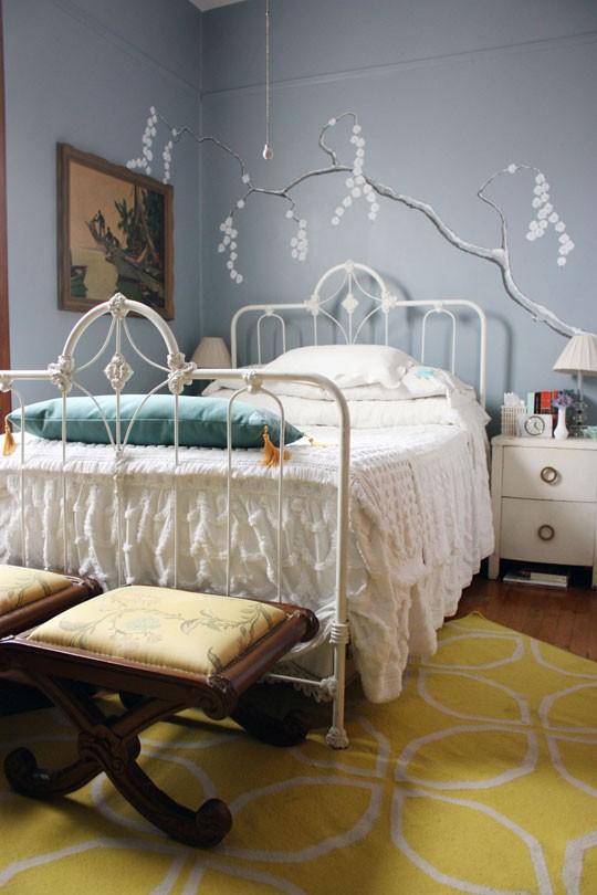 una camera da letto grigia decorata con un cuscino blu audace e alcuni tocchi di senape