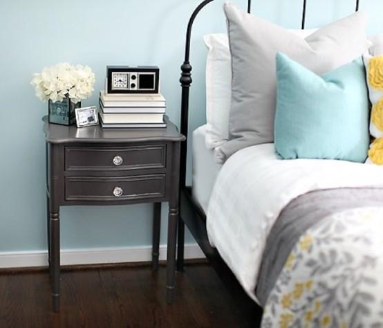 una camera da letto azzurra e biancheria da letto grigio, senape e azzurro