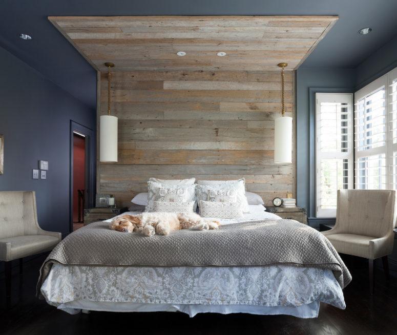 una piacevole camera da letto con una parte blu scuro e grigia separata da un grande tetto in legno stagionato sopra il letto, biancheria da letto grigia e mobili color crema