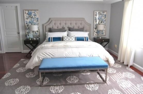 una camera da letto grigio chiaro decorata con cuscini blu audaci, una panca e opere d'arte