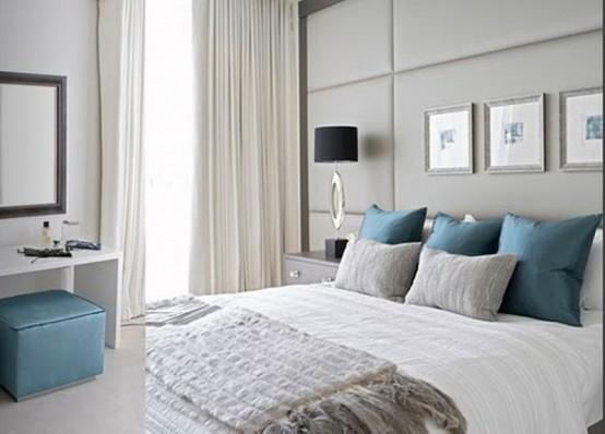una camera da letto grigio chiaro con cuscini blu audaci e un piccolo ottomano per aggiungere colore