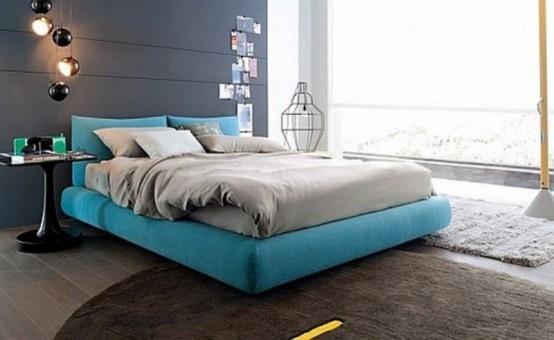 una camera da letto contemporanea con un muro di dichiarazione grigio grafite, un pavimento grigio e tappeti, un letto turchese e biancheria da letto grigia