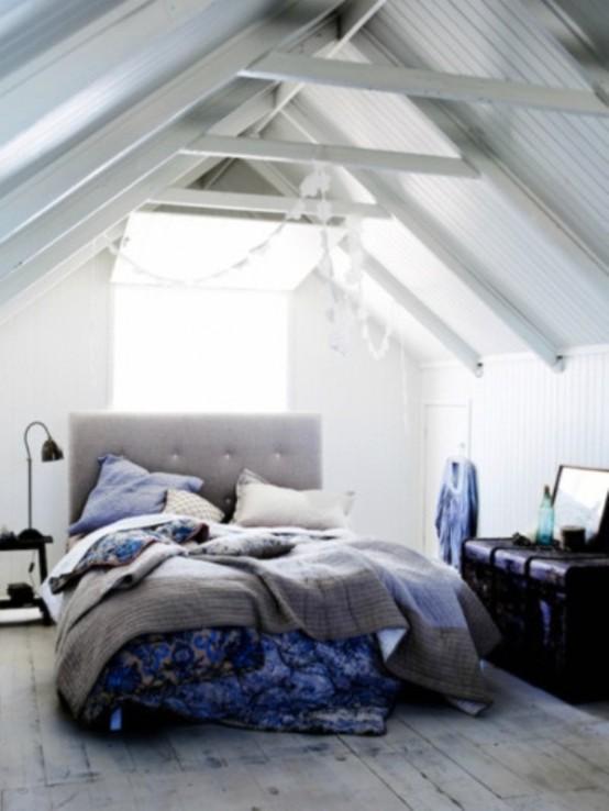 una camera da letto mansardata grigio chiaro e crema con un letto imbottito grigio e biancheria da letto grigia e blu