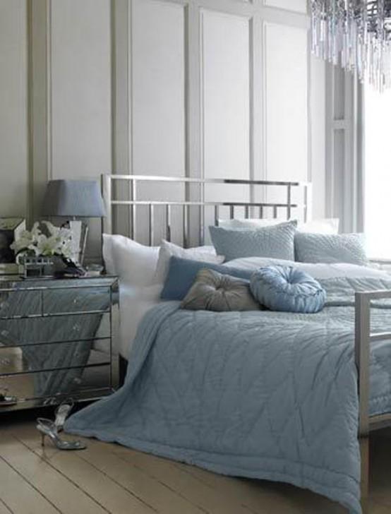 una camera da letto grigia con un letto finitura argento, un comodino a specchio e lenzuola blu e grigie