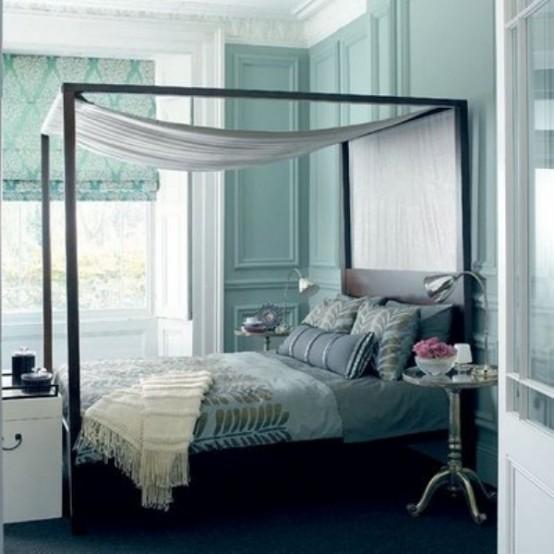 una camera da letto blu tiffany con un letto fatto con lenzuola grigie e argento e un baldacchino d'argento