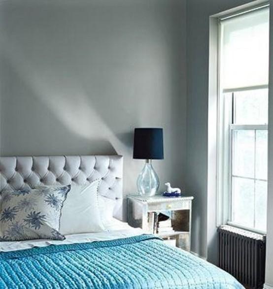 una camera da letto grigio chiaro, un letto imbottito grigio e una coperta turchese più lampade blu scuro