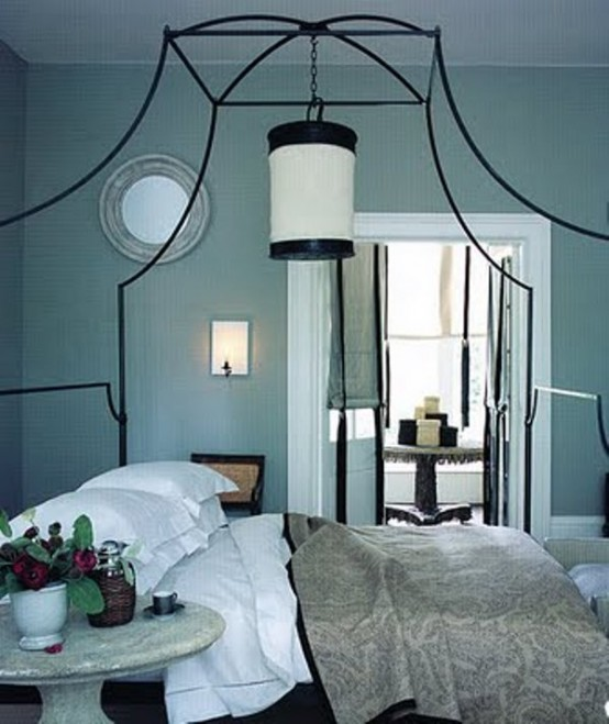 una camera da letto blu tiffany in stile vitnage, con un grande letto forgiato e biancheria da letto grigia