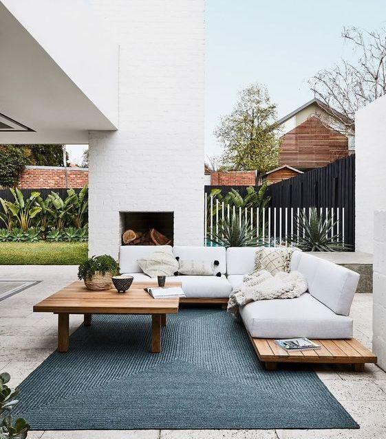 un soggiorno all'aperto con camino e comodi mobili di pallet più un bel tappeto blu