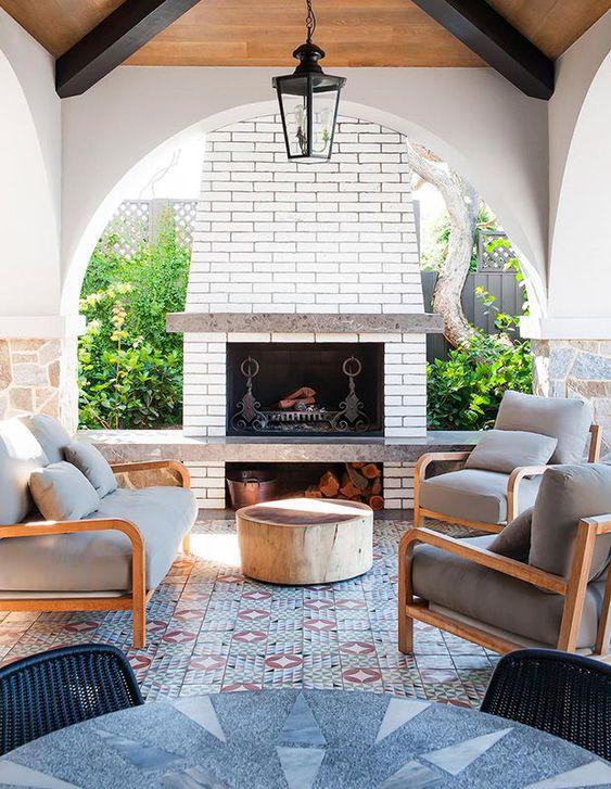 un luminoso salone all'aperto con camino, pavimento in piastrelle a mosaico e un tavolo audace più comode sedie