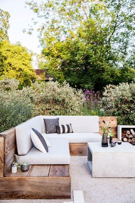 un soggiorno all'aperto con una grande panca e un tavolino in cemento più un supporto per legna da ardere