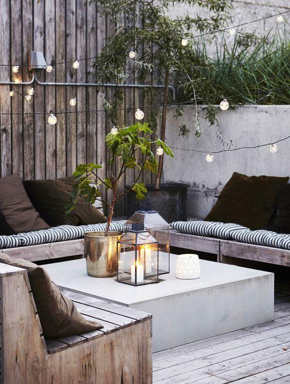 un accogliente salotto all'aperto con una panca a forma di U e un tavolino in cemento più luci dappertutto