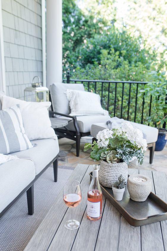 una fioriera ricoperta di filato e una di cemento, una lanterna e un po 'di vino e bicchieri