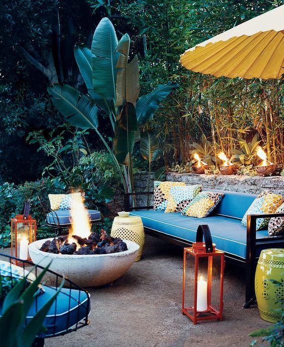cuscini colorati, lanterne rosse con candele, tavoli traforati e una grande ciotola per il fuoco per creare un ambiente