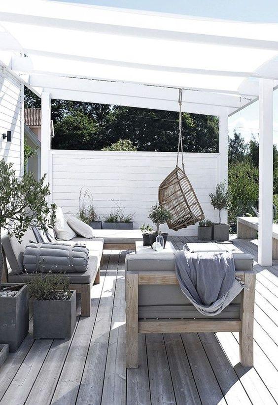 un accogliente salotto estivo con comodi mobili in legno e tocchi di cemento più una sedia in rattan