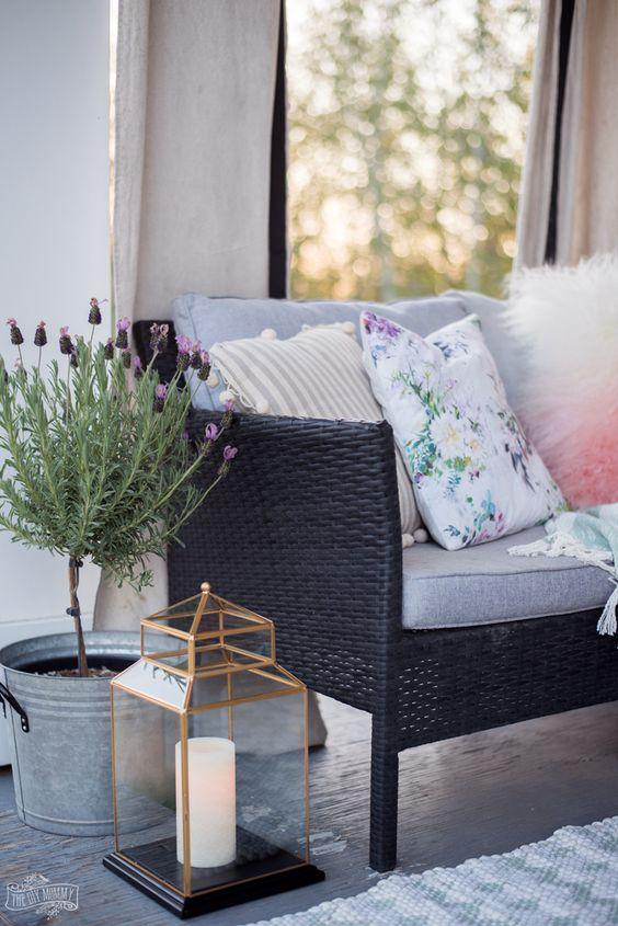 una lanterna a candela e fiori in vaso rendono questo spazio più accogliente e simile a un hygge