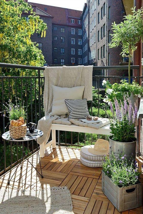 piante in vaso e fiori, un tappeto, cuscini e cesti rendono questo balcone accogliente