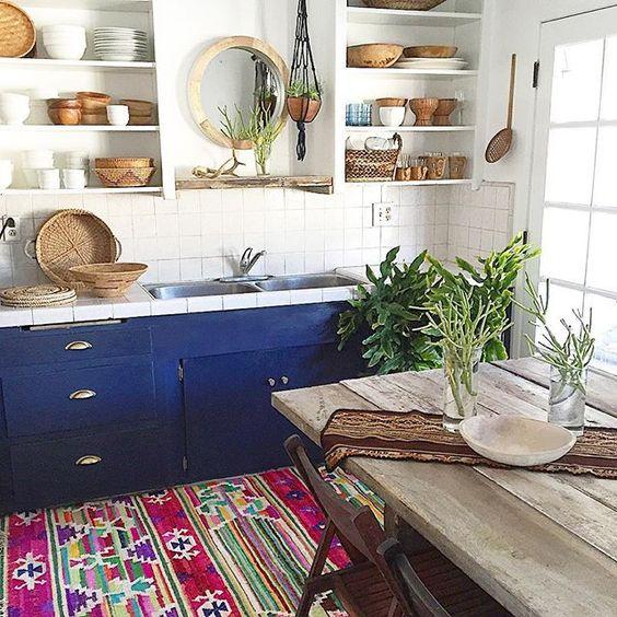 una cucina boho chic con tocchi in legno e vimini, più un colorato tappeto boho e armadi audaci