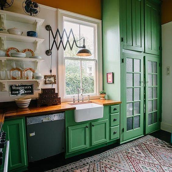 una cucina verde brillante con ripiani in legno e un tappeto colorato stampato si sente vintage