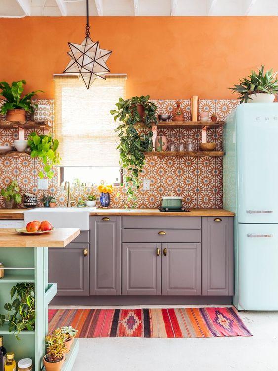 una cucina boho colorata con un muro arancione brillante, un frigorifero menta, armadi grigi con un piano in legno e un alzatina piastrellata stampata
