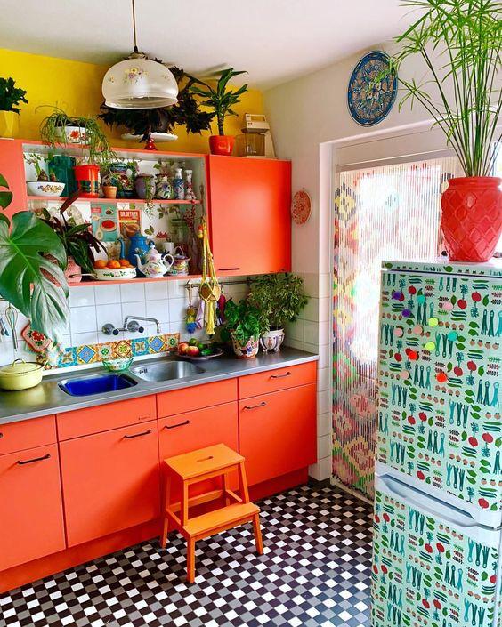 una cucina arancione brillante con pareti color senape, alzatina piastrellata e un frigorifero stampato più una tenda stampata