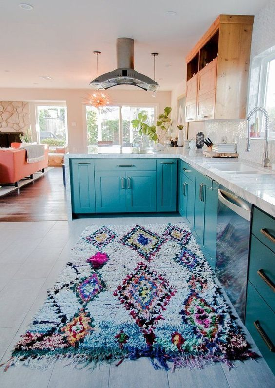 una luminosa cucina verde acqua con tomaia in legno e un colorato tappeto boho con frange